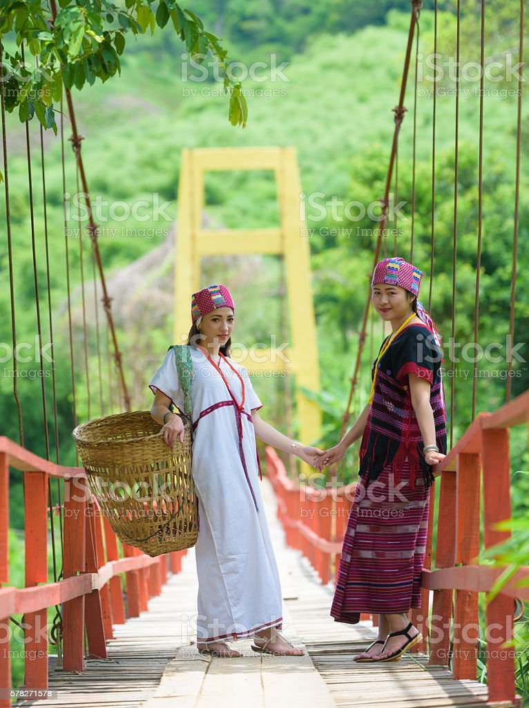 Traditionally dressed Karen hill tribe woman on rope bridge stock photo