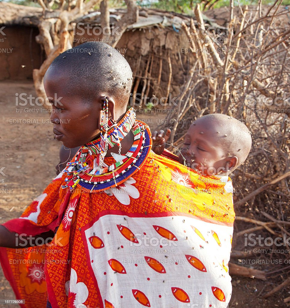 Traditionally dressed Masai mother with baby in swarm of flies. stock photo