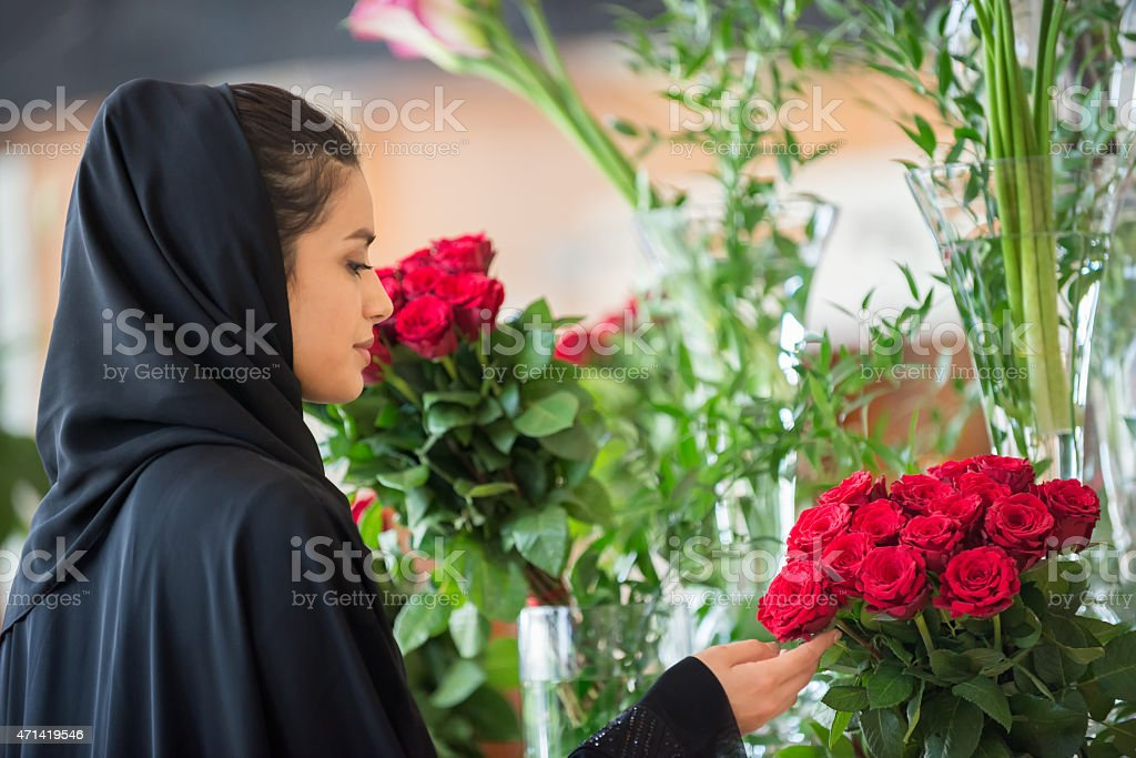 Traditionally Dressed Middle Eastern Woman Examining Red Roses in Vase stock photo