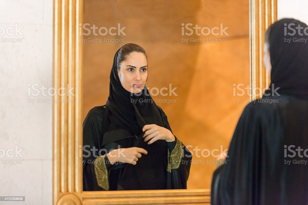 Traditionally Dressed Middle Eastern Woman Looking In Mirror, Adjusting Hijab stock photo
