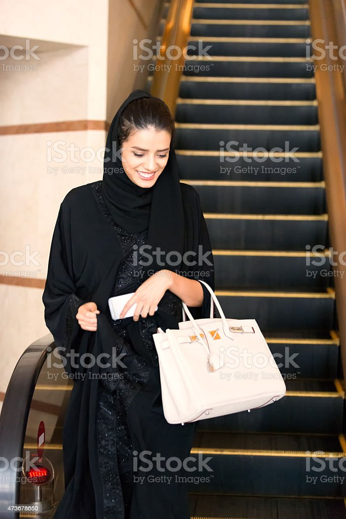 Traditionally Dressed Middle Eastern Woman Stepping off Hotel Escalator stock photo