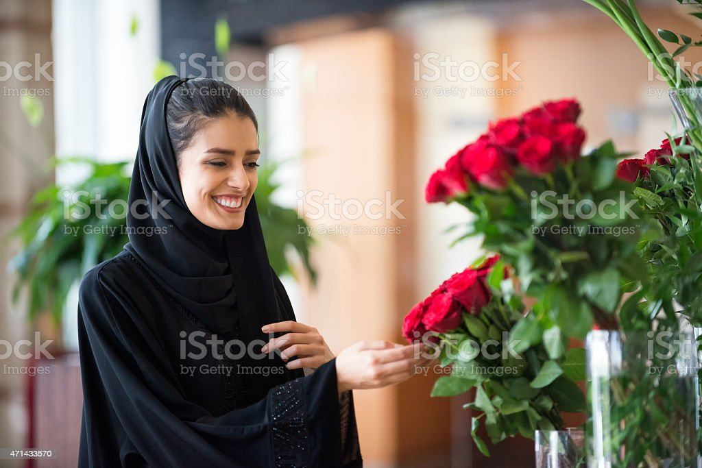 Traditionally Dressed Middle Eastern Woman Touching Red Roses in Vase stock photo