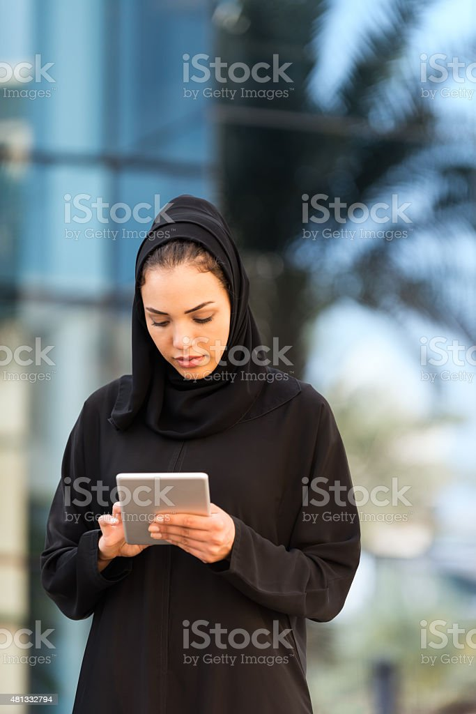 Traditionally Dressed Middle Eastern Woman Using Tablet Outside Modern Building stock photo