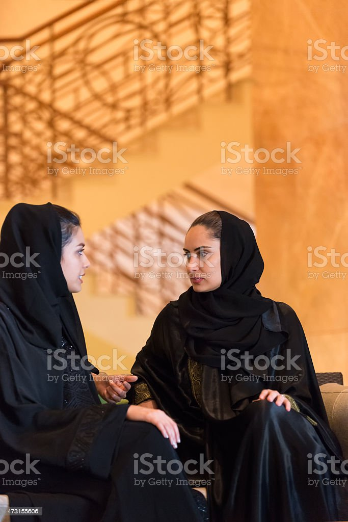 Traditionally Dressed Middle Eastern Women Having Discussion in Hotel Lobby stock photo