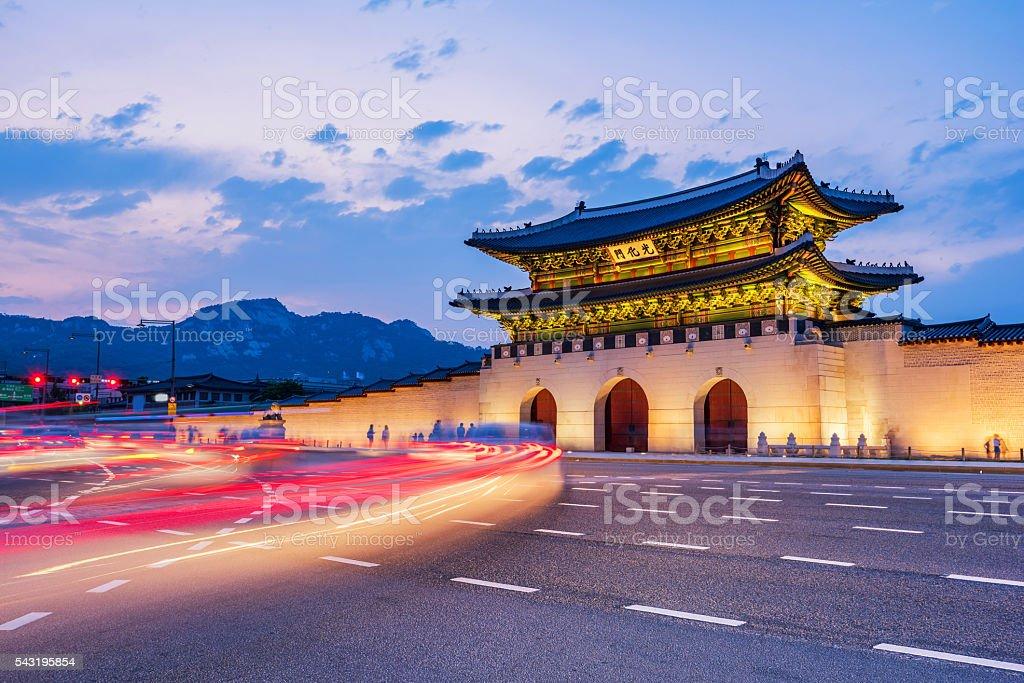 traffic blurs past Gyeongbokgung palace at night in Seoul, South stock photo