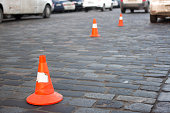 Traffic cone stay on paving stone  street. Limit for parking
