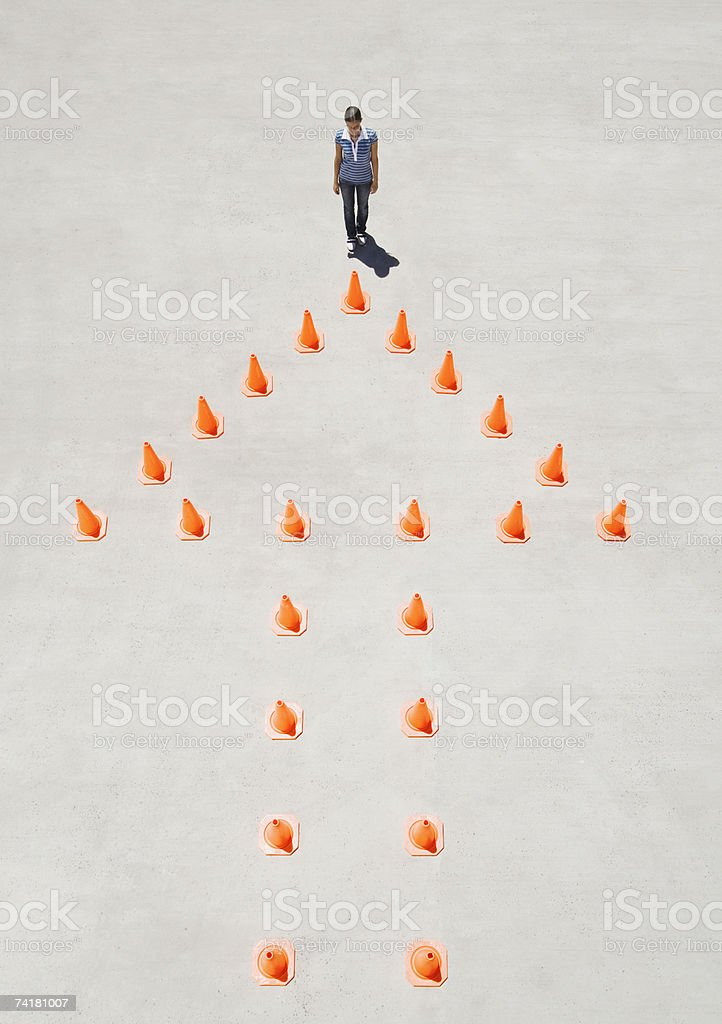 Traffic cones forming arrow with woman at top royalty-free stock photo