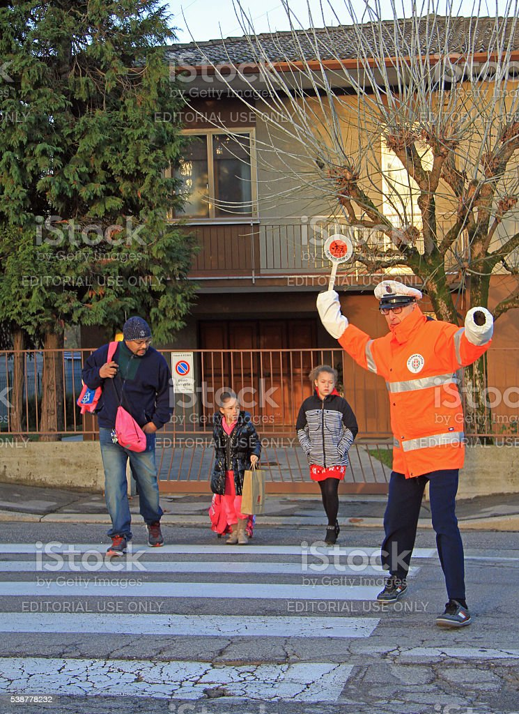 traffic controller is helping to cross a pedestrian crossing stock photo