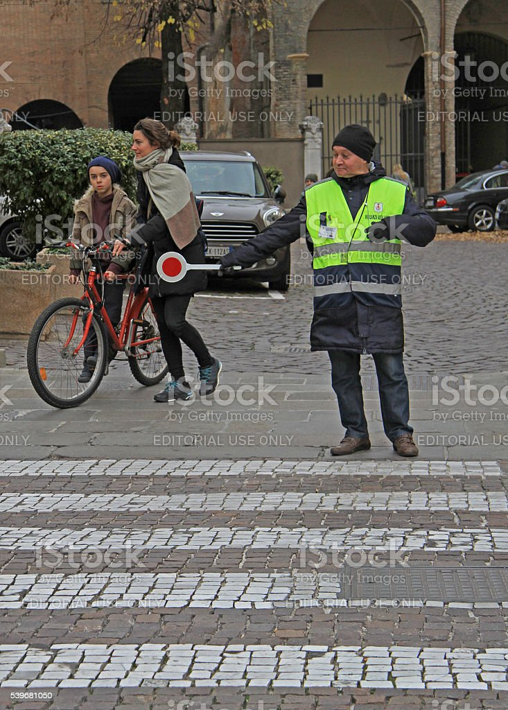 traffic controller is helping to people on pedestrian crossing stock photo