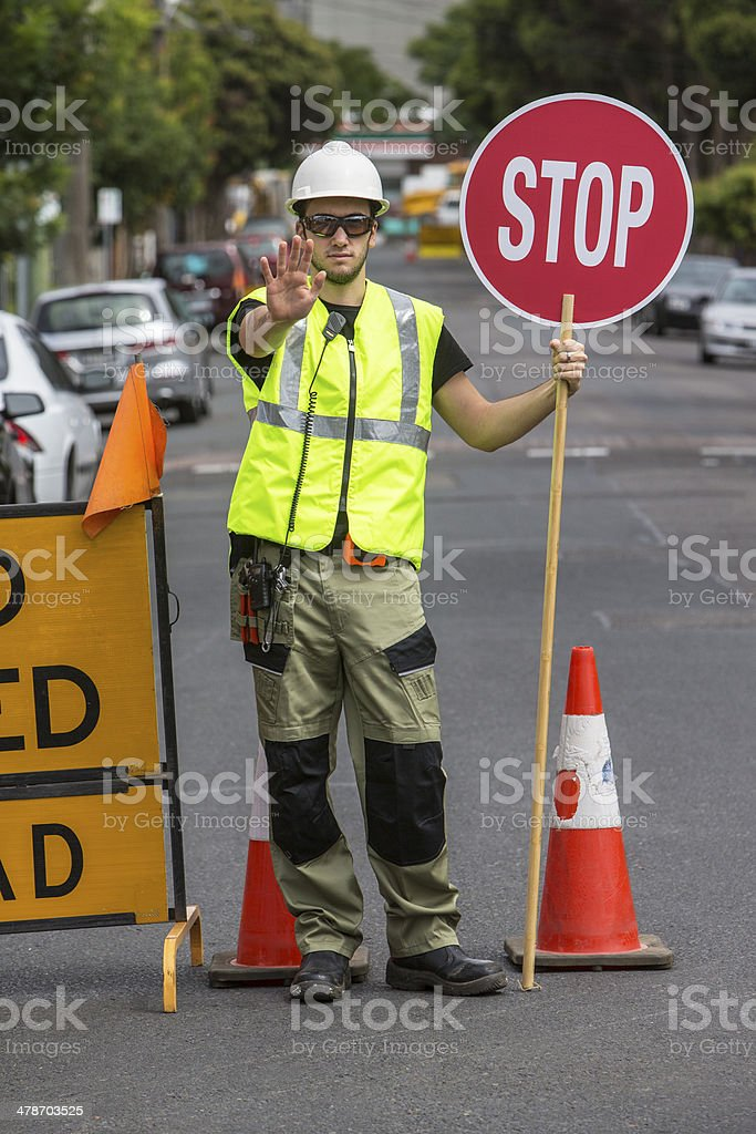 worker stopping traffic and holding stop sign stock photo