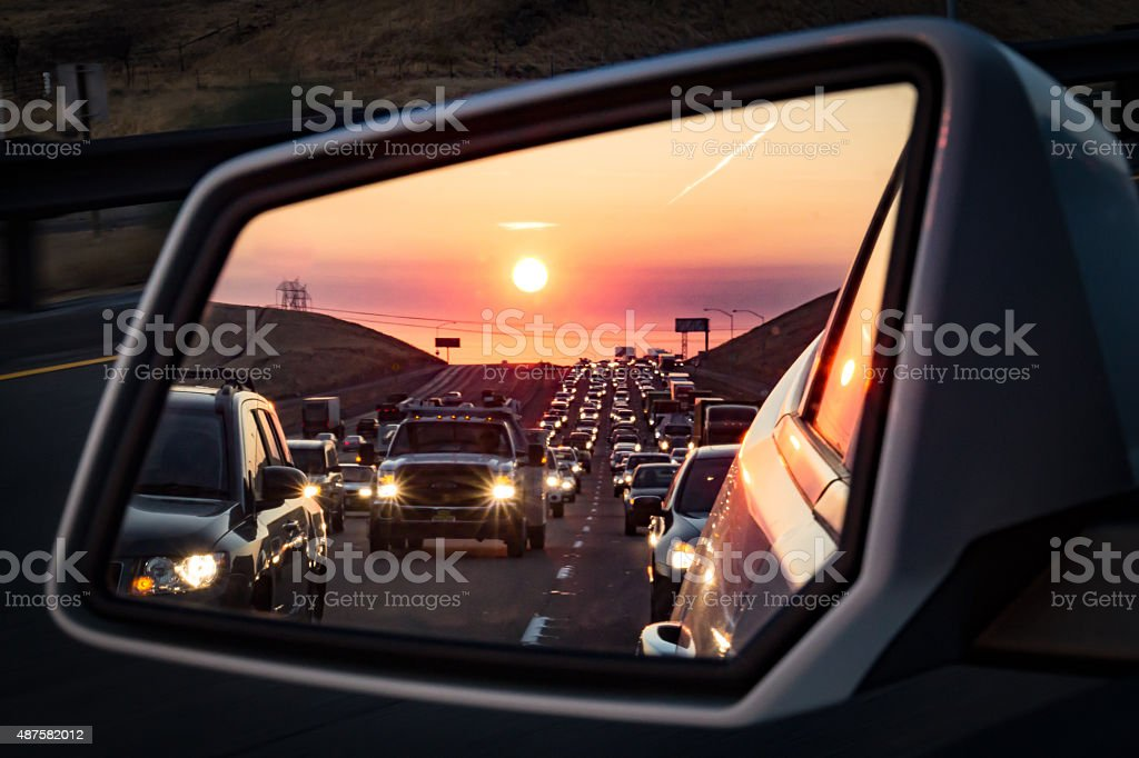 Traffic in the rearview mirror at sunrise stock photo
