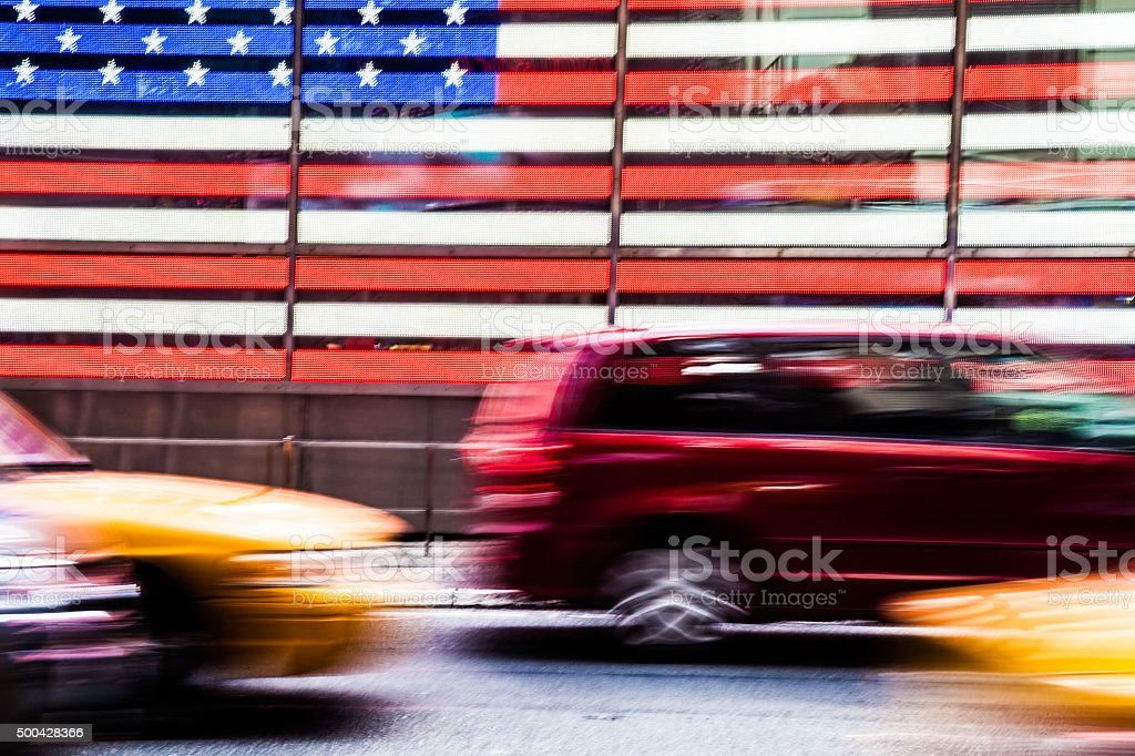 Traffic in Times Square in front of American Flag stock photo
