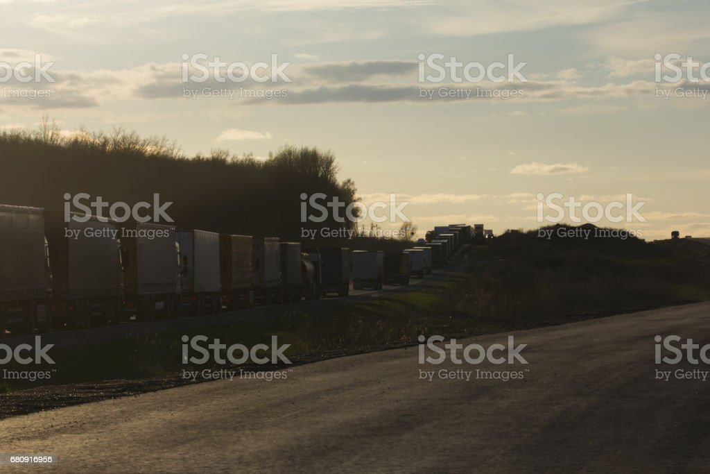 Traffic Jam of Heavy Trucks at Sunset - wide angle stock photo