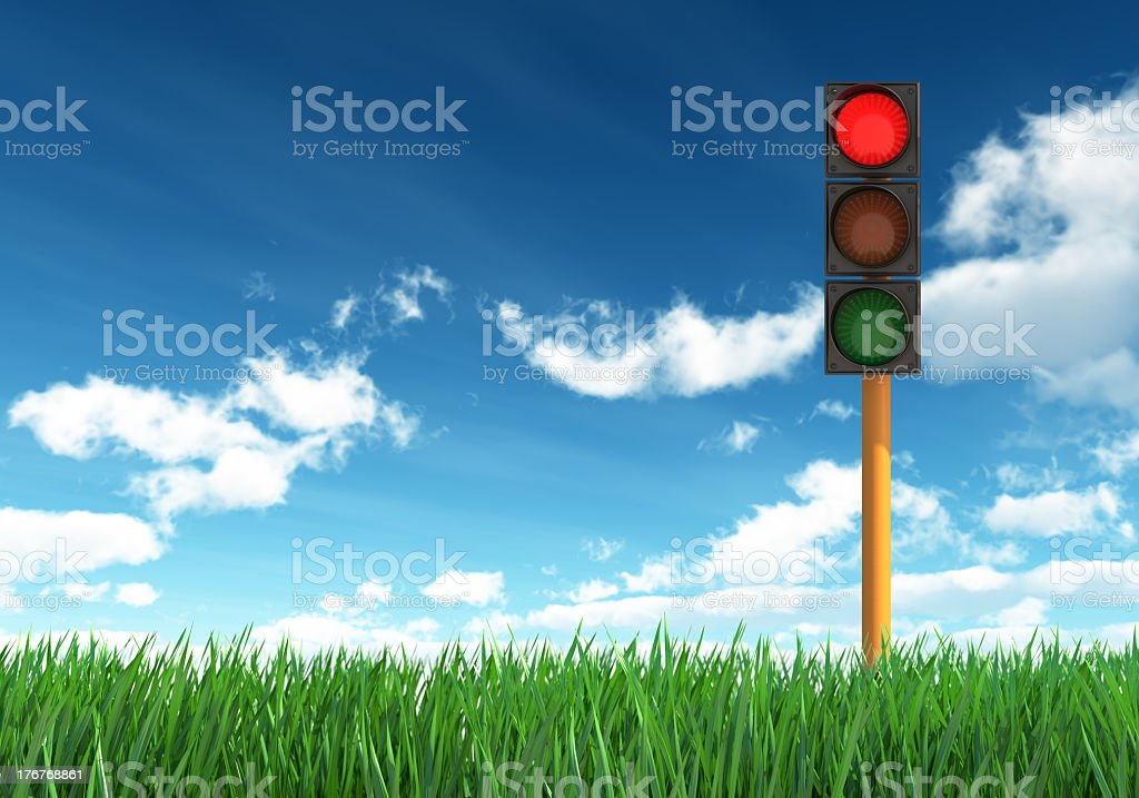 Traffic light on grass against blue and cloudy sky stock photo