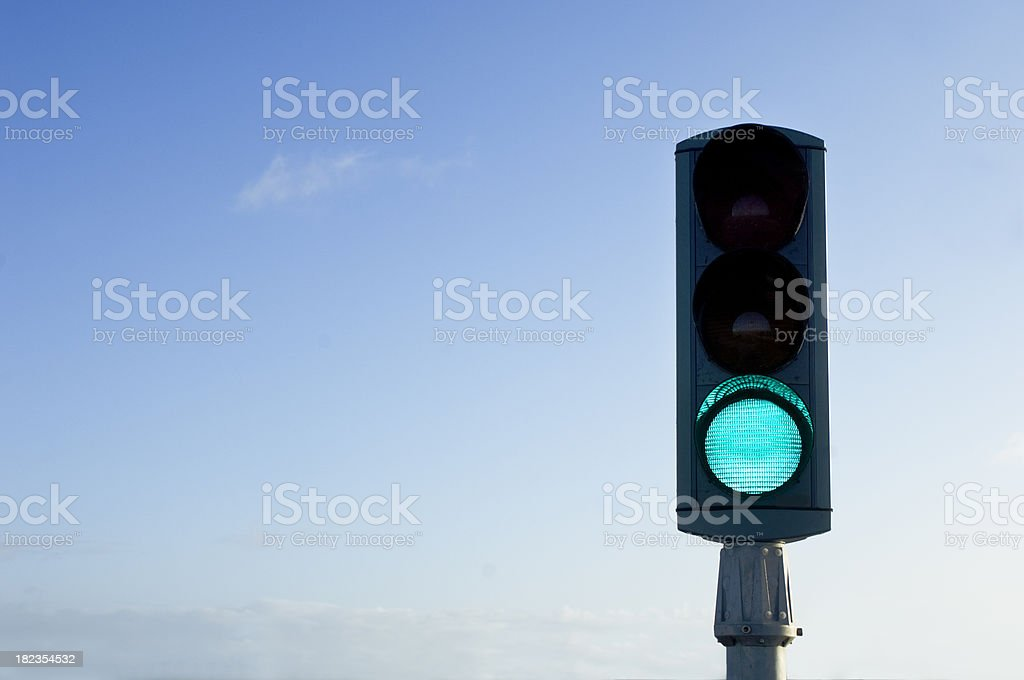 Traffic Light On Green For Go Isolated Against Blue Sky stock photo