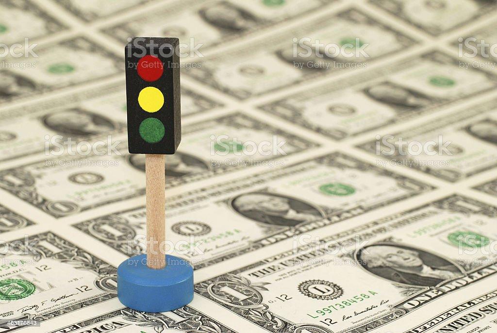 Traffic light (toy) standing on One Dollar Bills stock photo