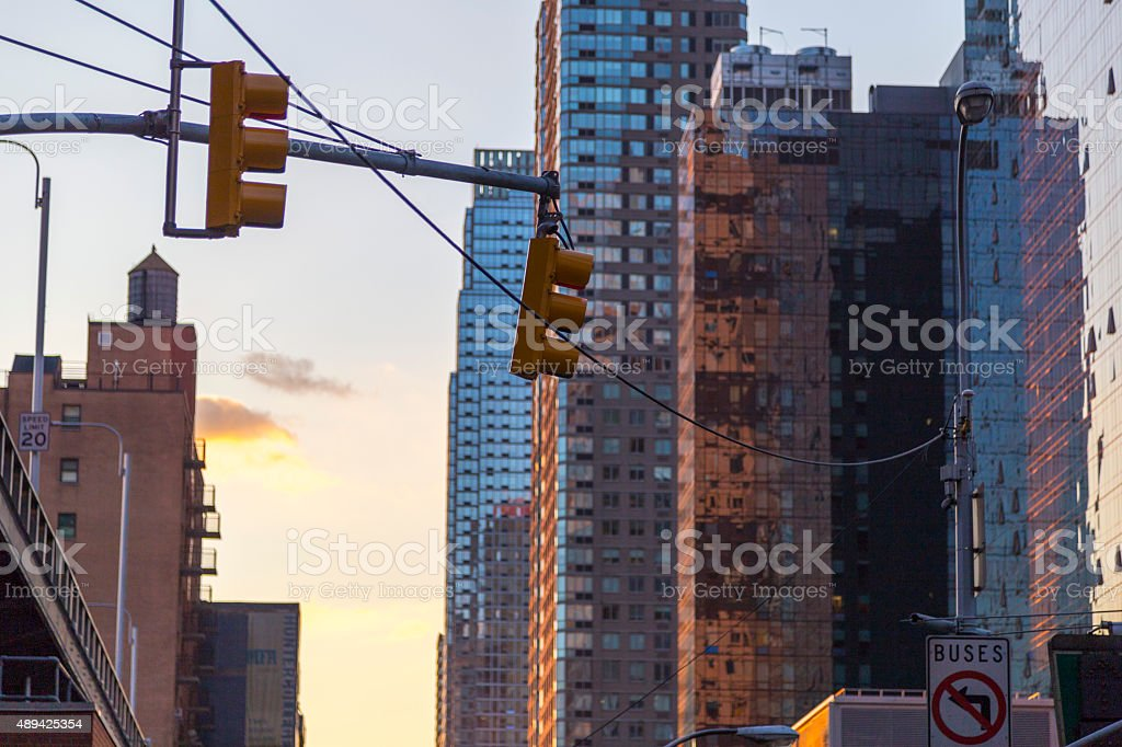Traffic light with skyscrapers in background in NYC at sunset stock photo