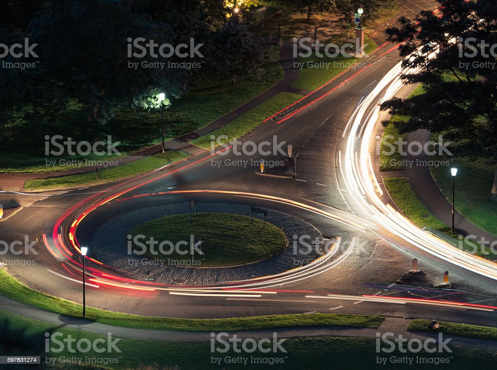 Traffic on a roundabout at night stock photo