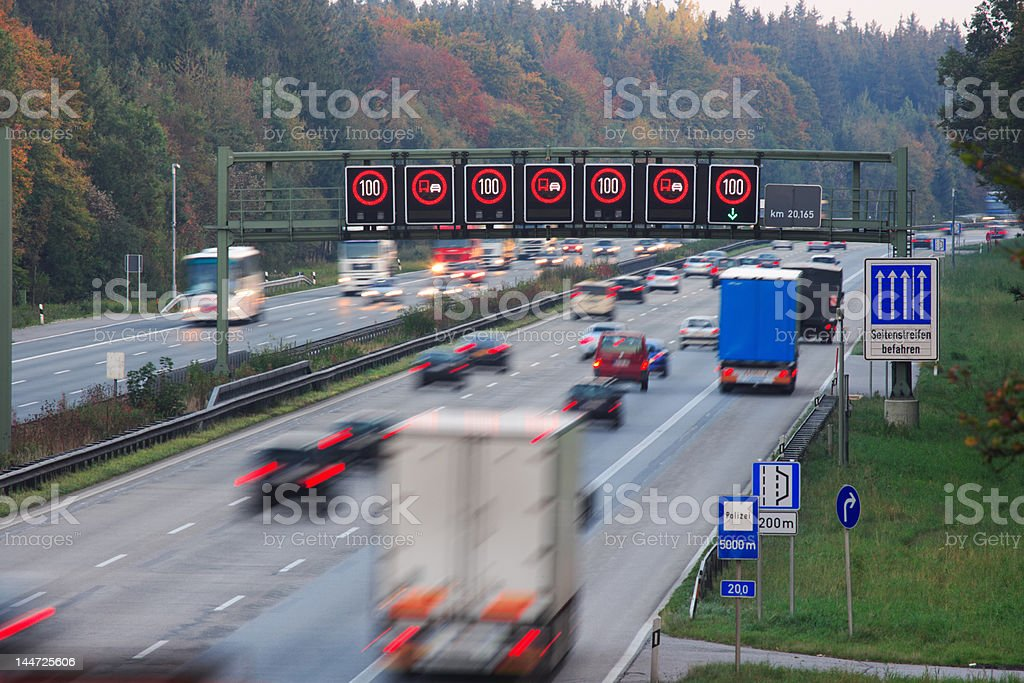 traffic on german autobahn with speed limit signs stock photo