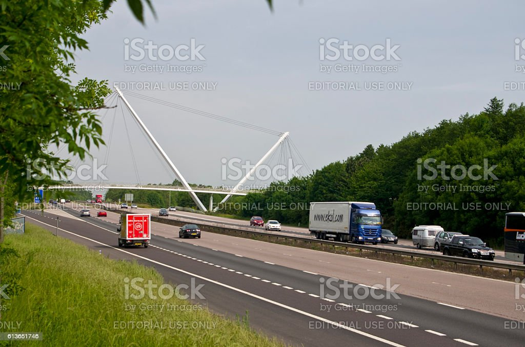 Traffic on motorway passes new Eureka Skyway pedestrian bridge Ashford stock photo