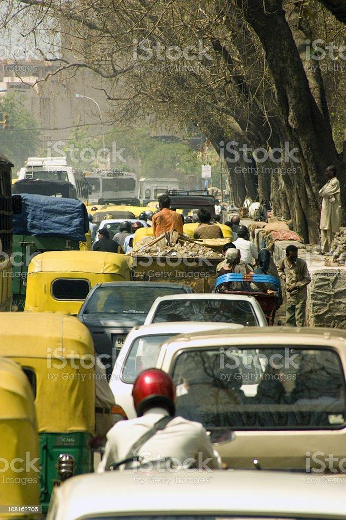 Traffic on Tree-Lined Road in New Delhi, India royalty-free stock photo