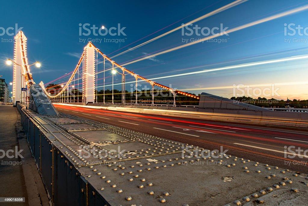 Traffic passes Chelsea bridge, London, at dusk stock photo