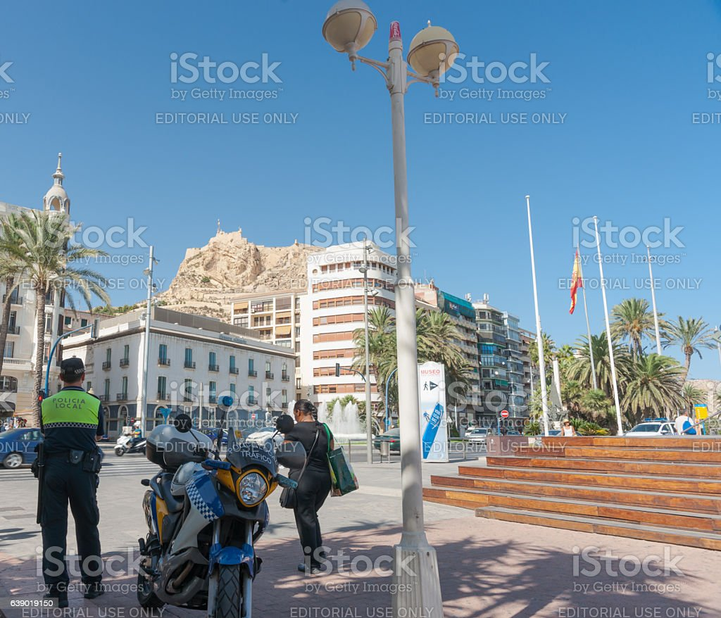 Traffic policeman with motorbike parrked in shade stock photo