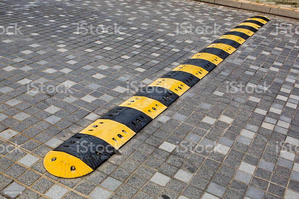 Traffic safety speed bump on an asphalt road stock photo
