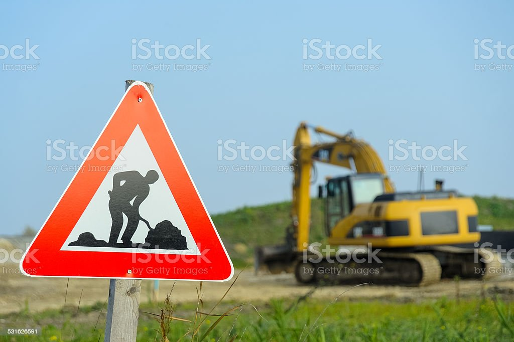 Traffic sign construction site with excavator stock photo
