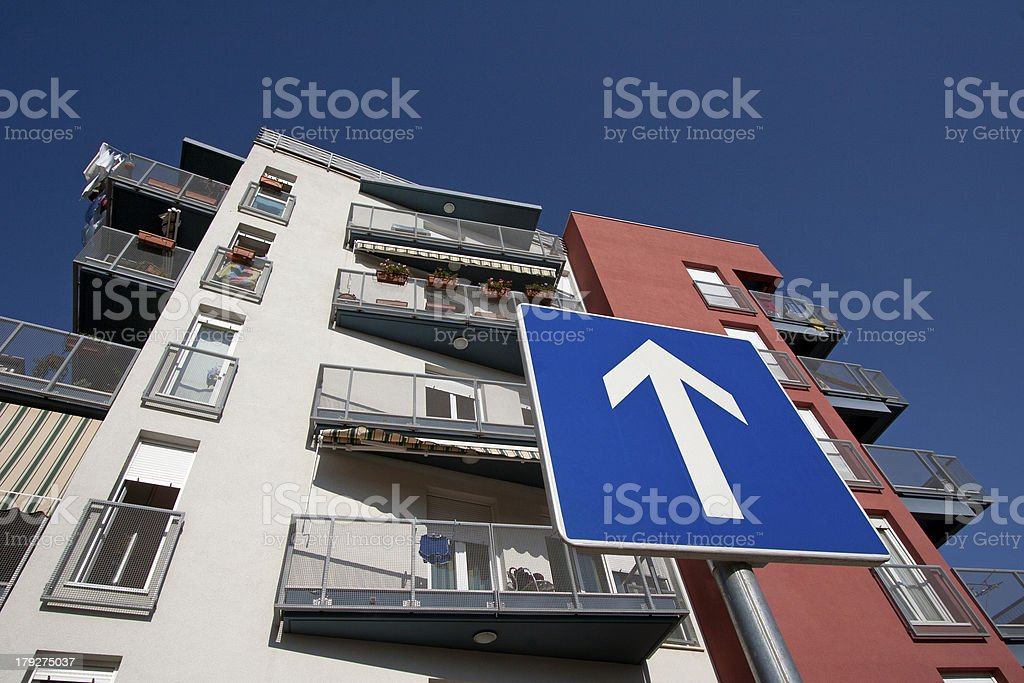 Traffic sign required direction in front of building facade royalty-free stock photo