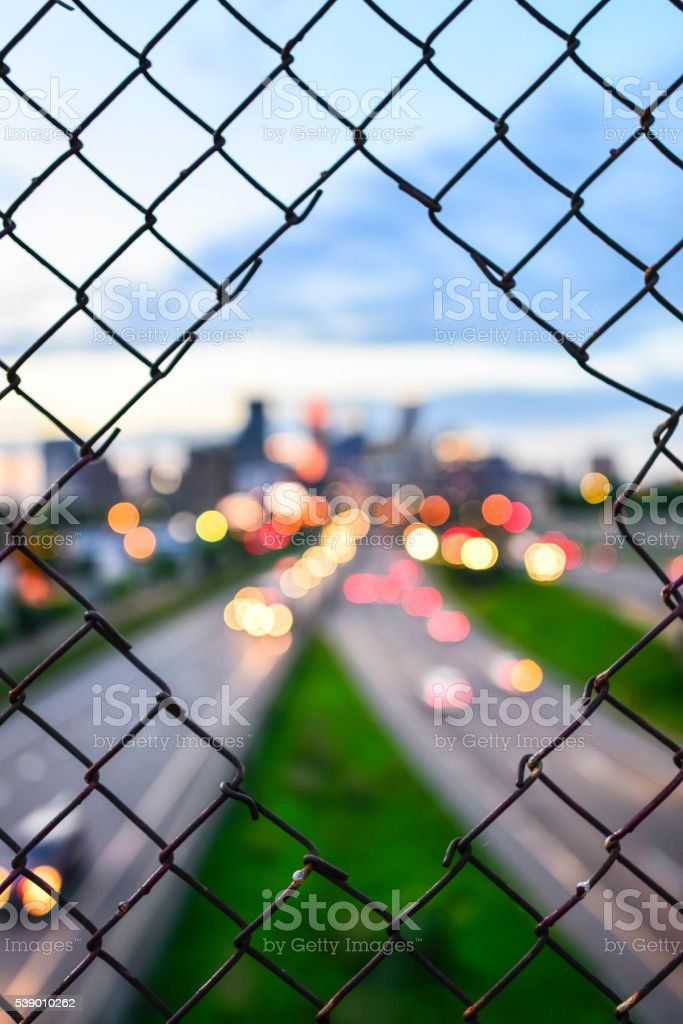 Traffic & Skyline Bokeh Through Cut Wire Fence in Minneapolis stock photo