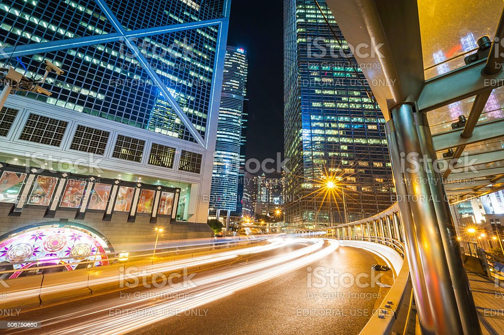 Traffic zooming through futuristic skyscraper city at night Hong Kong stock photo