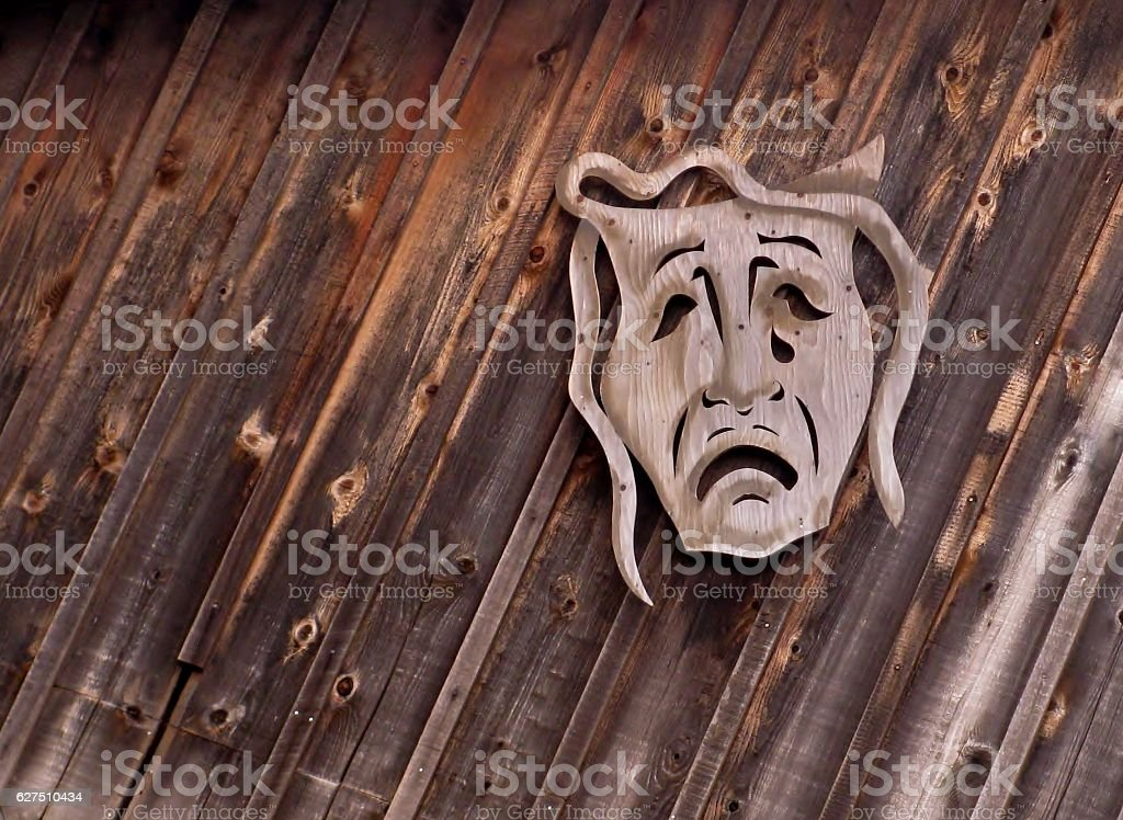 Tragedy theatrical mask on wooden background stock photo