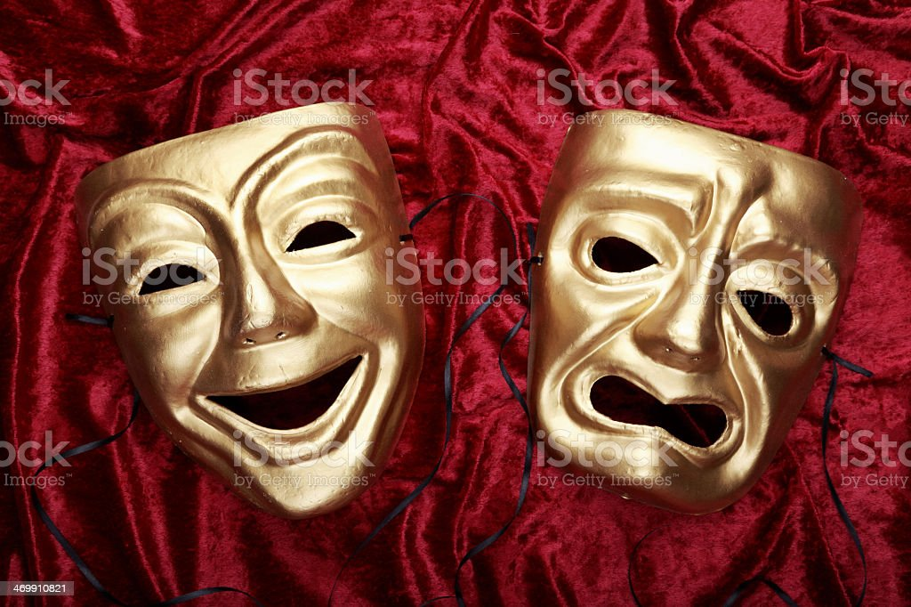 Tragic and comedic masks on red velvet stock photo