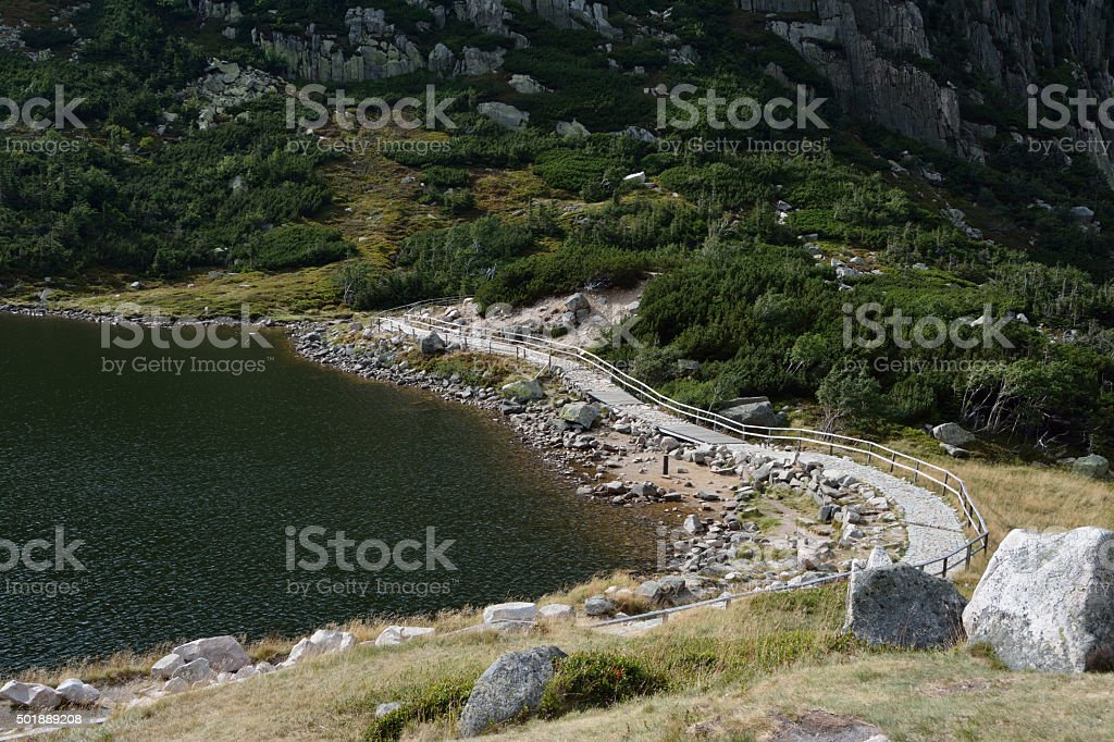 Trail at lake nearby Samotnia hill station in mountains. stock photo