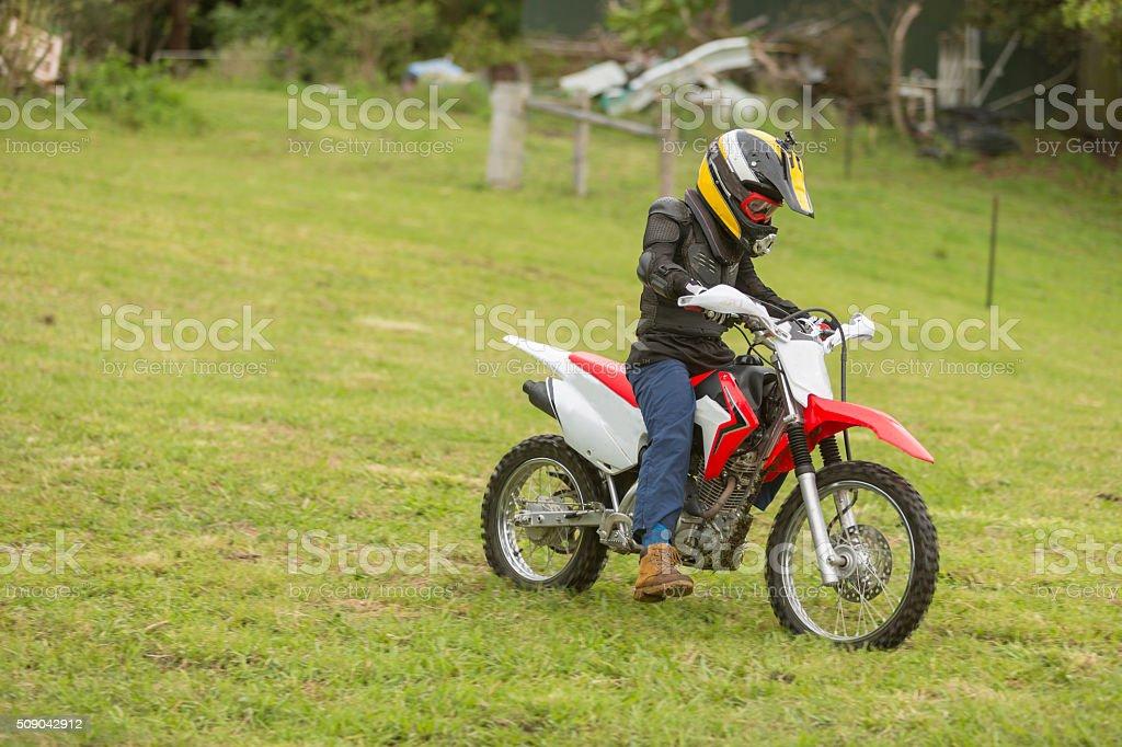 Trail Bike Riding Through a Paddock on a Farm stock photo