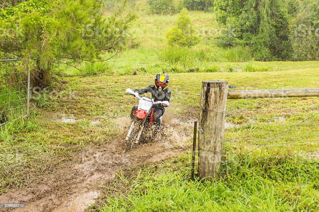 Trail Bike Splashing Through a Mud Puddle on a Farm stock photo