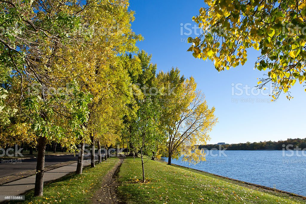 Trail in city park by lake in autumn stock photo