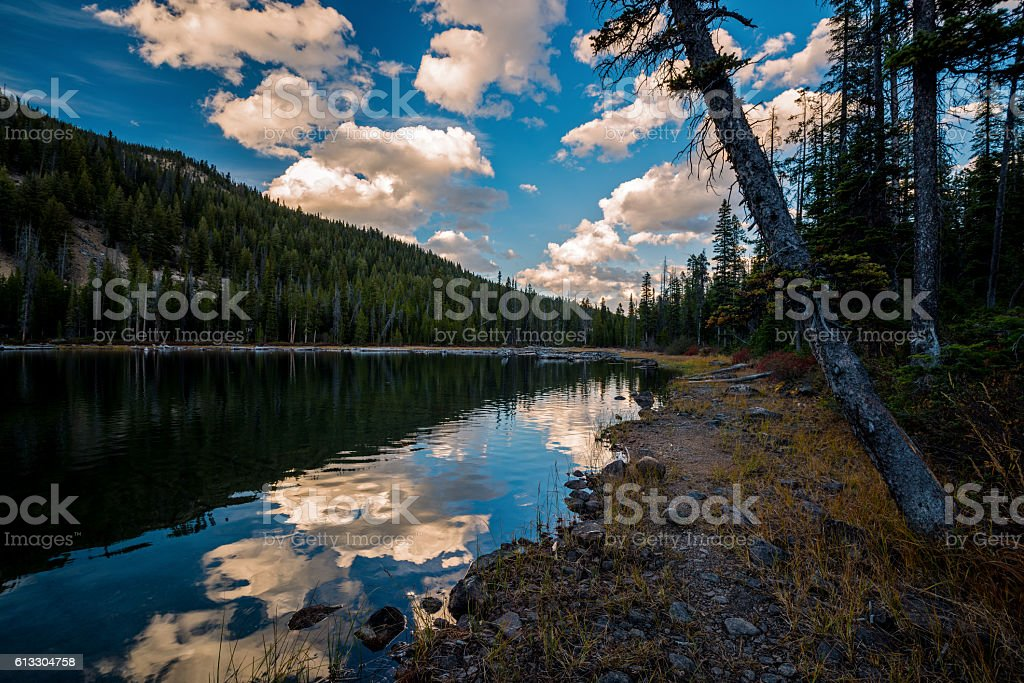 Trail leads on the shore of a lake at sunset stock photo
