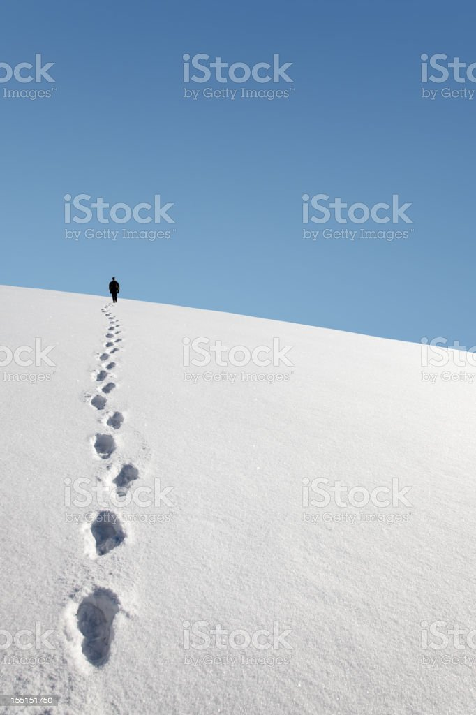 trail of footprints in the snow stock photo