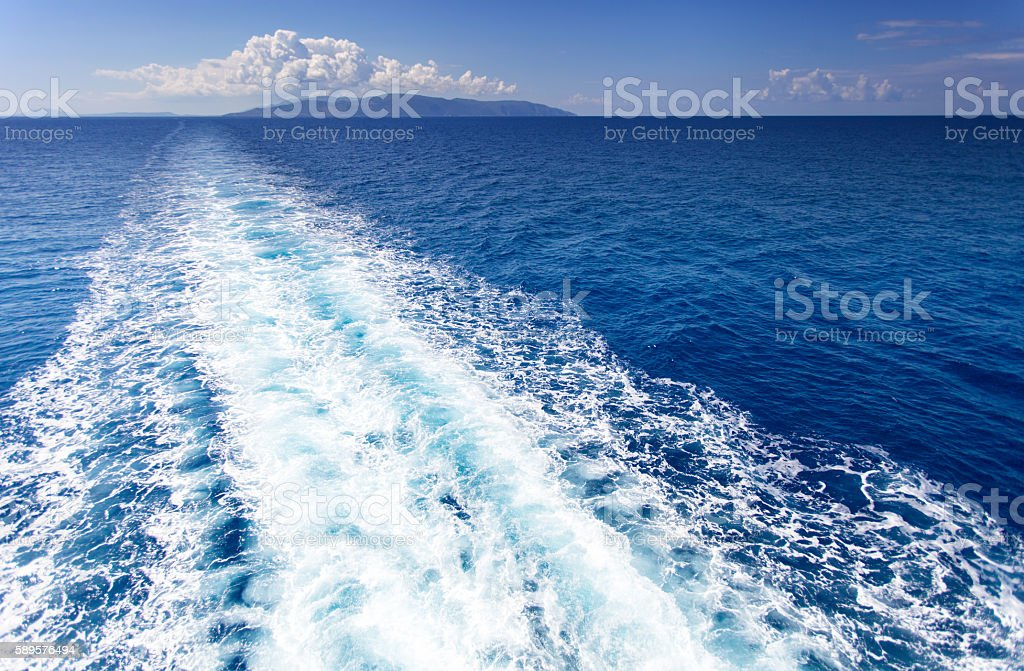 Trail on water surface behind of cruise ship stock photo