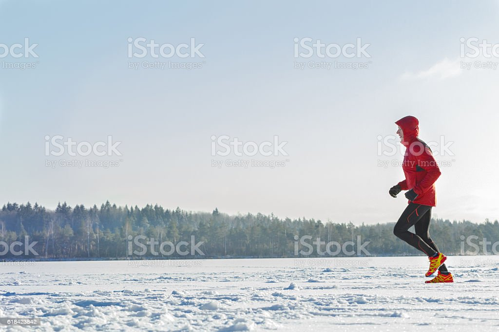 Trail racing runner wearing sportswear on winter training session outdoors stock photo