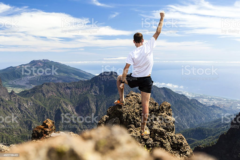 Trail runner succeeding by reaching the top of a mountain stock photo
