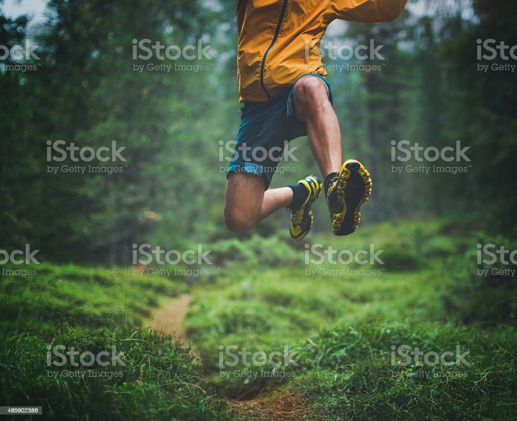 Trail running big jump stock photo