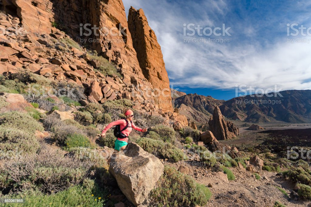 Trail running girl with backpack in mountains on rocky path stock photo