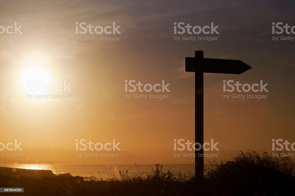 Trail sign post with seascape and sunset background. stock photo