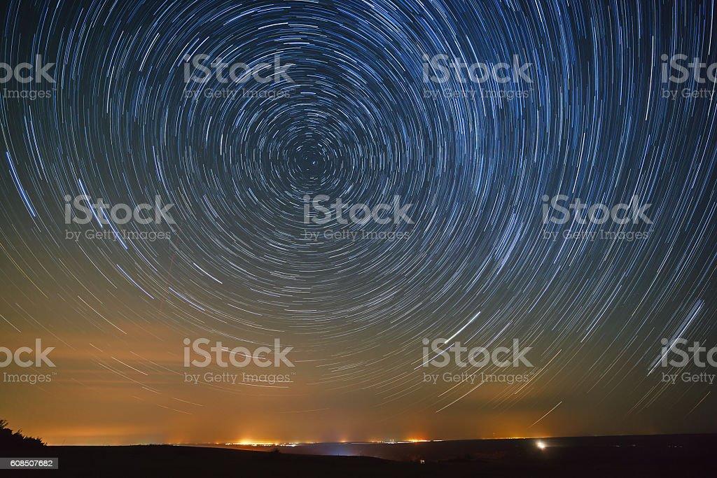 Trail stars around Polar Star the glowing over city. stock photo