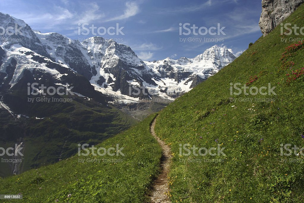 trail with snow-capped mountain stock photo