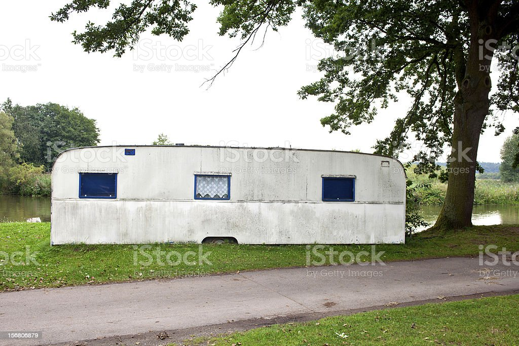 Trailer camp under tree on river bank. stock photo