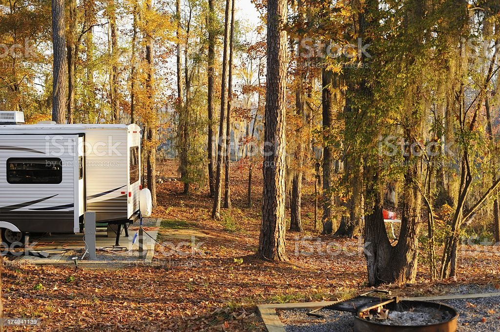 RV trailer in campground during morning or evening royalty-free stock photo